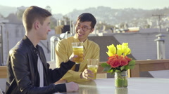 Mixed Race Gay Couple Cheers And Drink Beer On A Rooftop In San Francisco Stock Footage