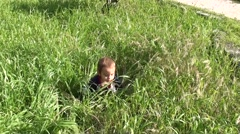 Baby finds a plastic bottle in grass Stock Footage