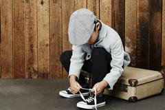 Boy tying shoelace on case Stock Photos