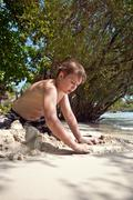 happy young boy is digging in the sand of the beach and constructing sand bui - stock photo