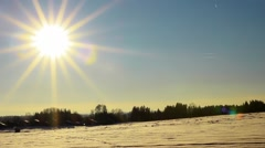 Time lapse of the moving sun over snowy field in the blue sky Stock Footage
