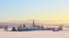 Time lapse of beginning sunset over a small hamlet in snowy mountain landscape Stock Footage