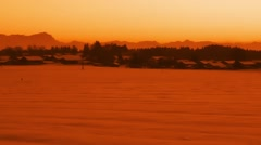 Sunset over a small country town with mountain skyline in snowy landscape Stock Footage