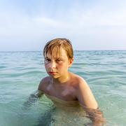 Angry young boy swims in the clear warm saltwater Stock Photos