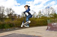 boy has fun going airborne with the scooter - stock photo