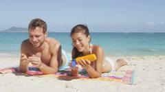 People on beach putting sunscreen suntan lotion - Sun tanning couple having fun Stock Footage