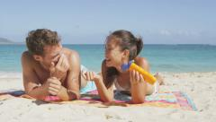 Honeymoon beach couple and sunscreen suntan lotion  laughing and relaxing Stock Footage