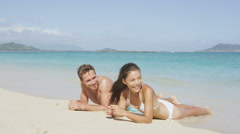 Beach vacations suntan couple relaxing on Hawaii - Blue sky and water Stock Footage