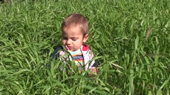 Crying baby in thick grass 2- - stock footage