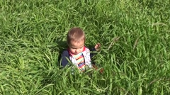 Crying baby in thick grass- - stock footage