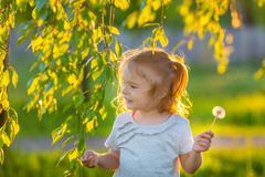 Stock Photo of Little girl in spring sunny park