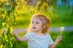 Little girl in spring sunny park - stock photo