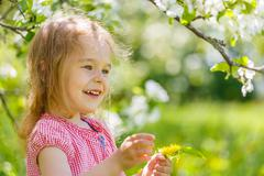 Happy little girl in spring sunny park - stock photo