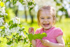 Stock Photo of Happy little girl in spring sunny park