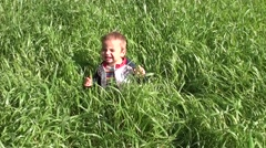 Unhappy baby in thick grass 2 - stock footage