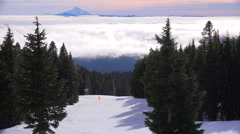 Skiers enjoy the slops of Mt. Hood, Oregon with Mt. Jefferson in the distance. Stock Footage