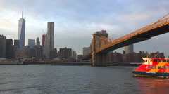 The lower Manhattan region with a water taxi passing. - stock footage
