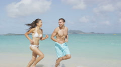 Happy couple having fun on beach vacation during summer holiday Stock Footage