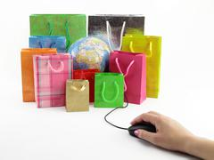 Computer mouse connected to a group of shopping bags with a globe inside Stock Photos