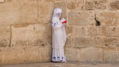 Jerusalem.  A loan woman reads a Christian prayer book against a wall. - stock footage
