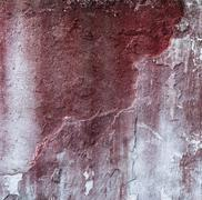 Broken concrete wall and faded red paint - stock photo