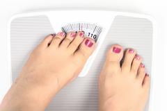 Woman' s feet on bathroom scale Stock Photos
