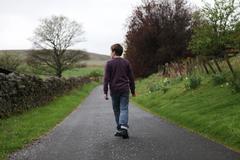 boy walking along empty countryside road in beautiful scenery - stock photo