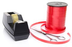 Roll of shiny red ribbon gift with scissors and scotch tape Kuvituskuvat