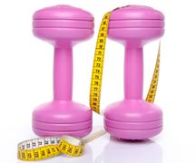 Pink dumbells with a tape measure - stock photo
