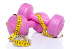 Pink dumbells with a tape measure Stock Photos