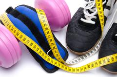 Pink dumbell, ankle weights and fitness shoes with a tape measure Stock Photos