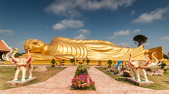 Timelapse of passing cloud over gold reclining buddha Stock Footage