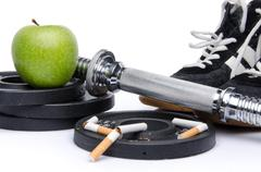 Dumbells, fitness shoes with an apple and broken cigarettes Stock Photos
