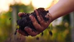 Farmer hand holding and pouring back organic soil Stock Footage
