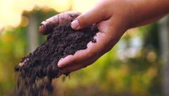 Farmer hands holding and pouring back organic soil Stock Footage