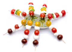 Cherry tomatoes and mozzarella on skewers and a vinaigrette sauce with basil - stock photo