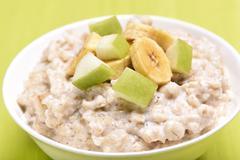 Porridge oats with apple and bananas slices - stock photo