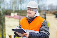 Construction employee with  documentation near building - stock photo