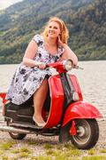 Red-haired beauty with overweight on a red scooter Stock Photos
