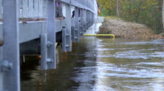 Stock Video Footage of Flooded River With Strong Currents Under Pedestrian bridge