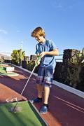 Jugendliche haben Spass beim Mini Golf spielen im Urlaub Stock Photos