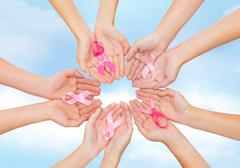close up of hands with cancer awareness symbol - stock photo