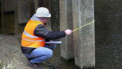 Engineer with tape measure and documentation under the bridge Stock Footage