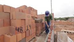 Bricklayer evens the cement on a brick - stock footage