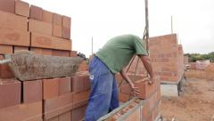 Bricklayer adjusting a brick on the wall - stock footage