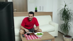 Man watching TV at home Stock Footage