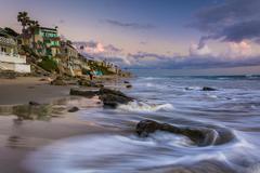 Waves crashing on rocks and beachfront homes in Laguna Beach, California. - stock photo