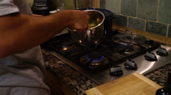 Young man cooking at home on the stovetop Stock Footage