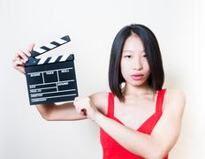 Young beautiful asian woman holding clapperboard white background Stock Photos