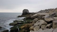 Rock stack on rocky coast by Portland Bill Lighthouse Dorset England UK Stock Footage